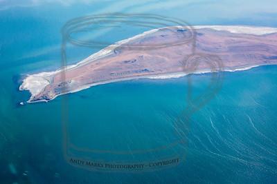 Arid dry island surrounded by shallow salt sea