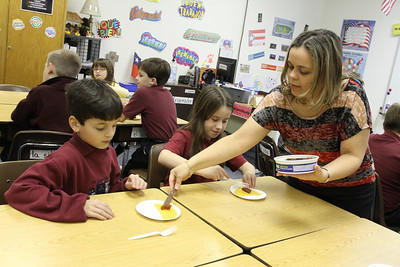 In her Feb. 9 Spanish class Elibeth Torres, right, serves up the ingredients for making empanadas to third-graders Gabriel Rodriguez and Alexandra Snyder.