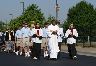 Father Henry Atem, parochial vicar at St. Peter Chanel Church, Roswell, leads the fifth annual procession of the Eucharist from the church to Fenway South, the outdoor ball field on the grounds of Queen of Angels School.