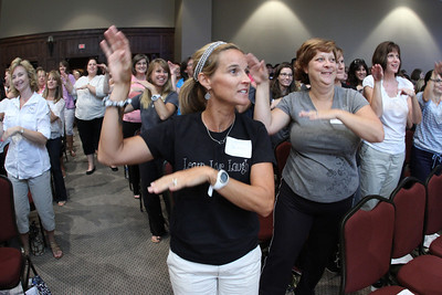 "Sheridan Tischendorf, center, and Kathy Turner, right, of St. Ann Church Preschool, Marietta, join keynote speaker Thomas Moore, PhD, and other attendees in doing the ""Humpty Dumpty"" dance."