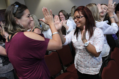"Silvia Barragan, left, and Daisy Collazo of St. Thomas the Apostle Church Preschool participate in a childhood game of ""Patty Cake."" It was one of several activities the keynote speaker engaged participants in during his keynote address."