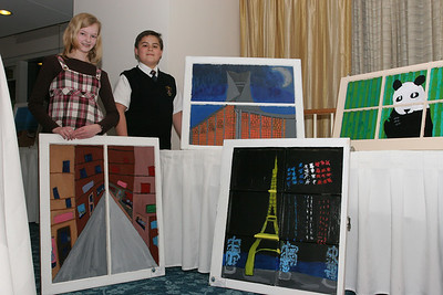 Laura Poole and Ethen Lund stand with their paintings A Look at Paris and L'église Sainte-Jeanne-d'Arc, respectively. Poole painted one of the Paris streets she went down from a past visit to the city. Lund painted the historic church dedicated to St. Joan of Arc. He and his family had an opportunity to visit the church in 2001.