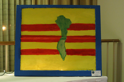"David Pham's painting is a tribute to his family's homeland of South Vietnam. Pham painted the country green over the backdrop of the South Vietnamese flag. Pham said, ""I painted the country green to symbolize the war and the people that were in it. I painted the frame blue to show the ocean east of the country."""