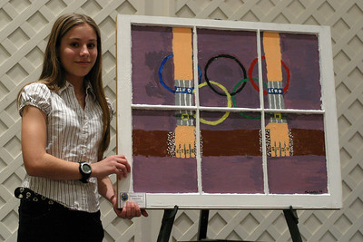 "Michaela Murphy, 13, stands by her painting of an Olympic gymnast. Murphy said, ""My window shows a gymnast on the uneven bars at the Olympics. The Olympics are a tradition for the earth; it is a way that we bond as one people on our one world. It brings all our cultures together and we can share them and pass them around the world."""