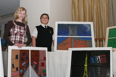 Laura Poole, left, and Ethen Lund stand with their paintings A Look at Paris and L'église Sainte-Jeanne-d'Arc, respectively. Poole painted one of the Paris streets she went down from a past visit to the city. Lund painted the historic church dedicated to St. Joan of Arc. He and his family had an opportunity to visit the church in 2001.