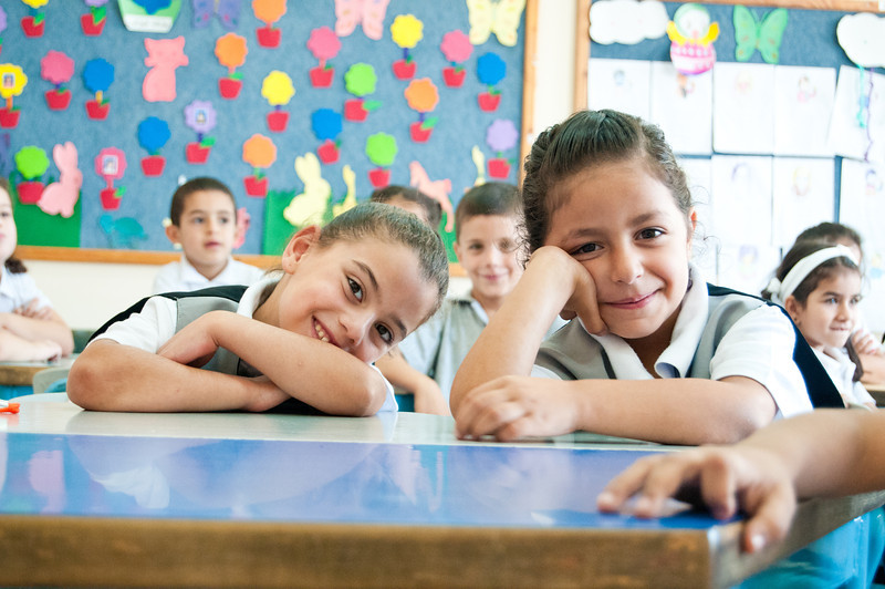 Grade 1 students smile shyly as the photographer sits in on their English class at Dar al-Kalima Evangelical Lutheran School in Bethlehem.  © ELCJHL/Rev. Elizabeth McHan