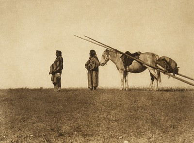 A travois - Blackfoot (The North American Indian, v. XVIII. Norwood, MA, The Plimpton Press,  1928), men, wearing blankets, horses, travois, transporting goods, poles