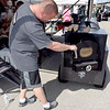 Nathan Dexter member of the Grey Street BBQ cooking team from Indiana checks the fire in his cooker during the KCBS State Championship EffingHAM-JAM held in downtown Effingham. Grey Street BBQ place third overall in Saturday's competition. Charles Mills photo
