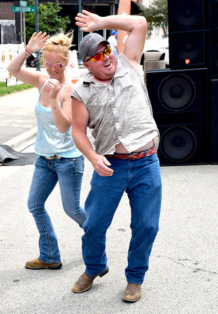 Stephanie Cropper of Barn Hill, Illinois, left and Jake Edgeworth of St. Peter, right, dance to the music of The Experienced in downtown Effingham on Saturday afternoon during the KCBS EffingHAM-JAM sponsored by the Effingham County Chamber of Commerce. Charles Mills photo