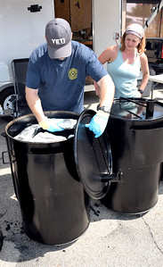 Grant Basihiere, left and Jina Basihiere of Gurnee, Illinois representing the QUE-U cooking team checks on their barbecue during the KCBS EffingHAM-JAM State Barbecue Competition held in Effingham over the weekend. Charles Mills photo