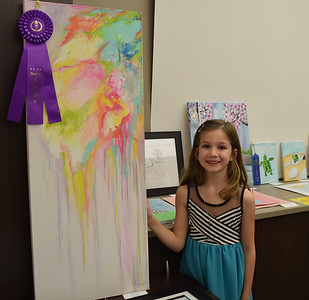 """Kathryn Uebinger, 7, Teutopolis, stands next to her Best of Show winner titled """"Paint Cloud,"""" for the PreK-4th grade category. The art show was hosted by the Effingham Art Guild for students across the county. Dawn Schabbing photo"""