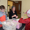 Volunteers fill cups with sugar and creamer to be used at the Effingham County FISH Human Services Annual Christmas Day Dinner held Christmas morning at the Sacred Heart Parish. Pictured from left to right, Payton Bushue of Mason, Carol Toney of Effingham and Carter Bushue of Mason. Charles Mills photo