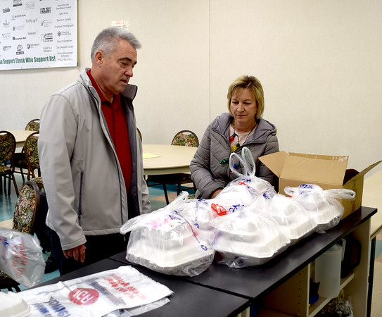 Jim Hecht, left, and his wife, Julie Hecht, right, count out 15 Effingham County FISH Human Services Annual Christmas Day dinners to be delivered to the Slate Creek apartments in Effingham. Charles Mills photo