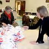 Barb Carie, left, and Carol Toney, right, count meals to be delivered throughout Effingham County on Christmas Day for the Effingham County FISH Human Services Annual Christmas Day dinner held at the Sacred Heart Parish Center in Effingham. Charles Mills photo