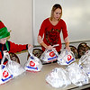 Volunteers Maddux Clark, left, and his mom Julie Clark, right, take meals to their family car on Christmas morning to be delivered throughout Effingham County for the Effingham County FISH Human Services Christmas Day Dinner. Charles Mills photo