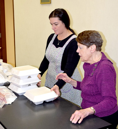 Volunteer Rebecca Holste, left, and Effingham County FISH Human Services Co-President Susan Elke, right, sort out meals Christmas day morning in the Sacred Heart Parish Center in Effingham. This is the second year the FISH organization has organized the annual community Christmas meal. FISH has organized the Thanksgiving Day meal for the past 14 years. Charles Mills photo
