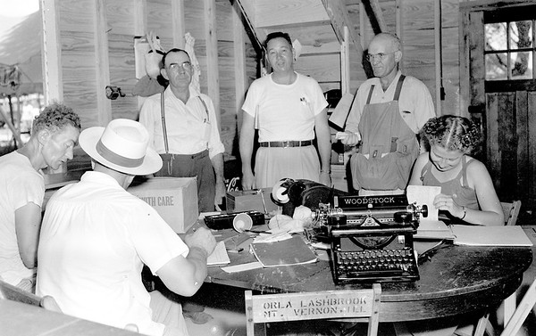 Fair officials responsible for the smooth operation of the 1949 Effingham County Fair are standing from left to right, Ben Reiss, president of the fair association, Milton Smith, treasurer and concession supervisor, John Russell, superintendent of gates and Mrs. Marion Merry, office assistant secretary.<br /> Seated in front is a man representing Harris stables, far left, registering his horse for the society horse show. The man with his back to the camera is Mart Alwert, fair secretary. EDN file photo