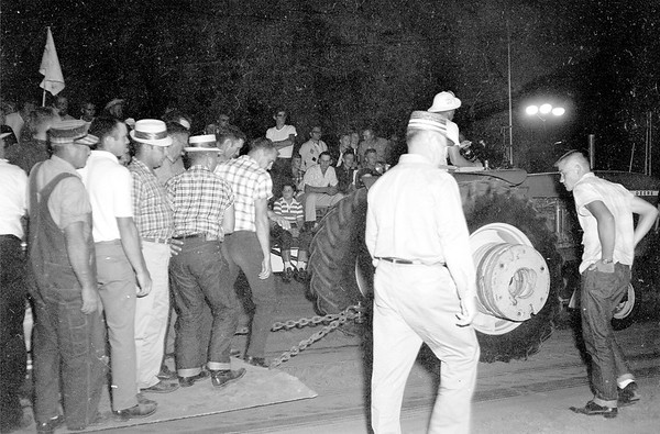 In earlier tractor pulling days before the modern day weight sled, humans provided the weight one by one stepping on to a piece of metal pulled behind the tractor until the tractor could not pull any further. Pictured is a tractor pull from 1965. EDN file photo