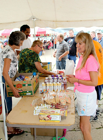 Jamie Nance, right, helps visitors load trays of food at the Effingham FreedomFest Saturday at the Village Square Mall. The event provides food from local food pantries, games, music and a meal, which is all offered free of charge.<br /> Tony Huffman photo