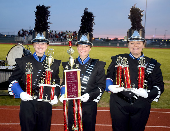 Newton Community High School Marching Eagles drum majors, from left to right, Haylee Schoonover, Emma Pitcher and Emily Ross hold their trophies their band won Saturday evening during the Effingham Marching Hearts Invitational band contest. NCHS Marching Eagles were named Grand Champion of the Class 3A and Class 4A band divisions. Charles Mills photo