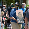 A demonstrator holds a drawing of George Floyd, the man who was killed in May after a Minnesota police officer knelt on his neck for nearly nine minutes.