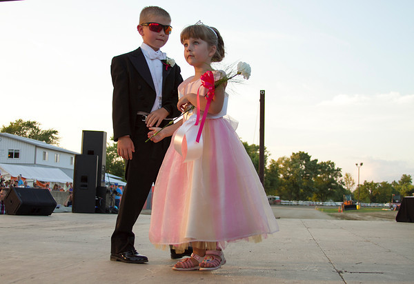 A contestant of the Effingham County Fair Little Miss Pageant takes the stage with the help of an escort Tuesday. Each of the Little Miss participants were assisted by a young escort while walking in front of the crowd. | Photo by Cassie Porter