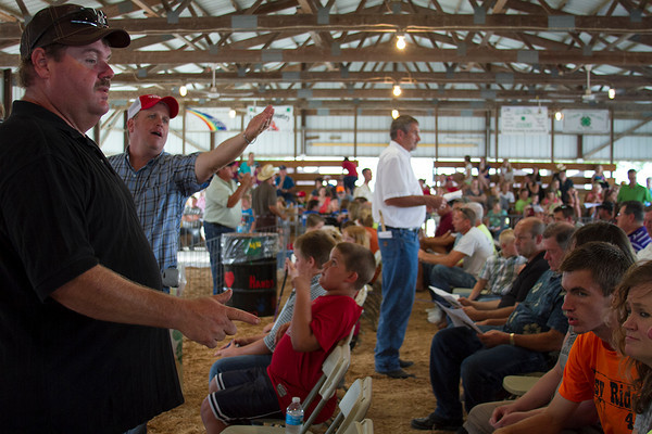 Mark Stoneburner, left, of Beecher City and Trent Schmid of Teutopolis keep an eye on bidders during the 4-H Auction at the Effingham County Fair in Altamont. The auction had a variety of different animals, from rabbits to cows.   Photo by Cassie Porter