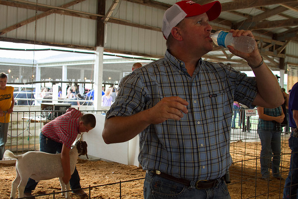 Trent Schmid of Teutopolis takes a quick water break as a 4-H member brings in an animal to be auctioned Wednesday at the Effingham County Fair 4-H Auction. | Photo by Cassie Porter