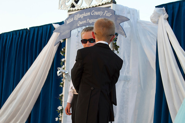 Two young escorts for the Little Miss portion of the Effingham County Fair Queen Pageant wear sunglasses Tuesday as part of their outfit while walking Little Miss participants across stage. | Photo by Cassie Porter