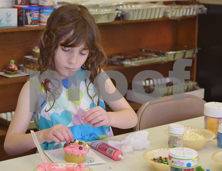 Leanorah Scott of Kirkland, 7, decorates a cupcake Saturday during the Easter Eggstravaganza at Genoa Faith United Methodist Church. Scott said cupcake decorating was her favorite event of the day.