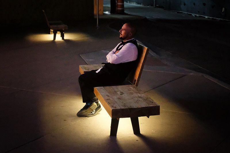 """El Paso Strong<br /> El Paso, TX  (2019)<br /> <br /> This is Gerard, the doorman at a historic downtown theater. He's waiting for the end of the night's performance - a poetry reading to raise funds for """"El Paso Strong,"""" the organization formed in response to the hate crime where a gunman killed 22 and wounded 24 on August 3, 2019. <br /> <br /> """"I grew up in LA,"""" he said. """"There, everyone is always rushing to get to where they're going. Here, it's not like that. People still say, """"Yes, Ma'am"""" and """"No, Sir"""" and they'll hold the door for you.""""<br /> <br /> """"The disappointing thing is that El Paso has always been the safest city in the US. Since that shit at the Walmart, whenever anyone thinks of us, it's something different."""""""
