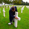 Sand from Omaha beach being rubbed into the engravings on Uncle Harold's grave.