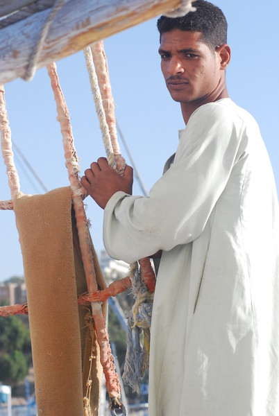 Felucca boatman on the Nile River wearing a traditional galabea