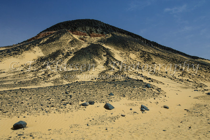 A mountain of black volcanic rock mixed with sand in the Black Desert of the Western Desert of Egypt.
