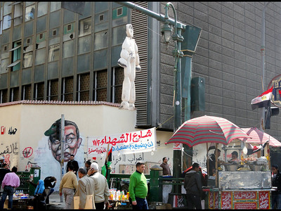 Tahriri Square: Corner of Mohamed Mahmoud Street and Tahrir Square: mural on wall blends one in the same faces of rejected President Hosni Mubarak and Field Marshall Mohamed Hussein Tantawi, leader of SCAF.
