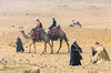 Tourists riding camels near the Pyramids of Giza, Egypt.