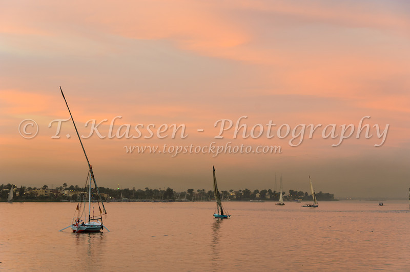 Felucca sailboats on the Nile River at sunset near Luxor, Egypt.