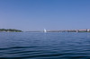 The wide expanse of the Nile River and a lone felucca sailboat near Aswan, Egypt.