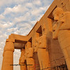 Line of giant Osiris statues at sunset at the Ramesseum, the ancient egyptian mortuary temple of Ramses II at thebes near Luxor, Egypt