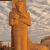 giant Osiris statue lit by late sunlight at the Ramesseum, the ancient egyptian mortuary temple of Ramses II at thebes near Luxor, Egypt