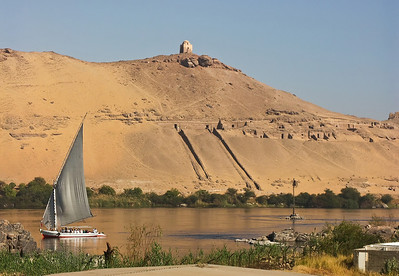 A felucca on the Nile with some ruins in the background.