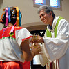 Father Jes˙s Flores accepts the gifts during the annual Bienvenida Mass June 27 at Brockport's Nativity of the Blessed Virgin Mary Church.