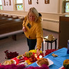 Mary Beth Cecchini leaves a note for her dad, who passed away six years ago, on the ofrenda set up at St. Thomas Aquinas for Day of the Dead. In Mexican tradition, notes for deceased loved ones are placed alongside their favorite foods and drinks on an ofrenda, typically a small altar in a family's home.
