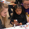 Mikayla Johnson, right, helps Nicole Ruiz put glue on a paper skeleton puppet during the Day of the Dead celebration while Alex Dennie watches. Johnson and Dennie, both freshmen at York Central School, volunteered at the event after learning about Day of the Dead traditions in their Spanish class.