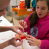 Hanna Wolfgange, right, makes a paper flower with help from Emily Carney, a junior at York Central School. Carney volunteered at the Day of the Dead celebration with other classmates after learning about the tradition in a Spanish class.