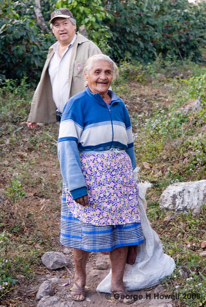"""I had to take her photo: her happy nature radiated in body language and declarative speech as she walked past us.  In the words of Sergio: """"She is 78 years old and her name is María Deras. She is Manuelito's mother, our administrator. She grew up in the surroundings of Finca Los Planes and she has been a picker since she was 18 years old.""""  That is Sergio in back."""