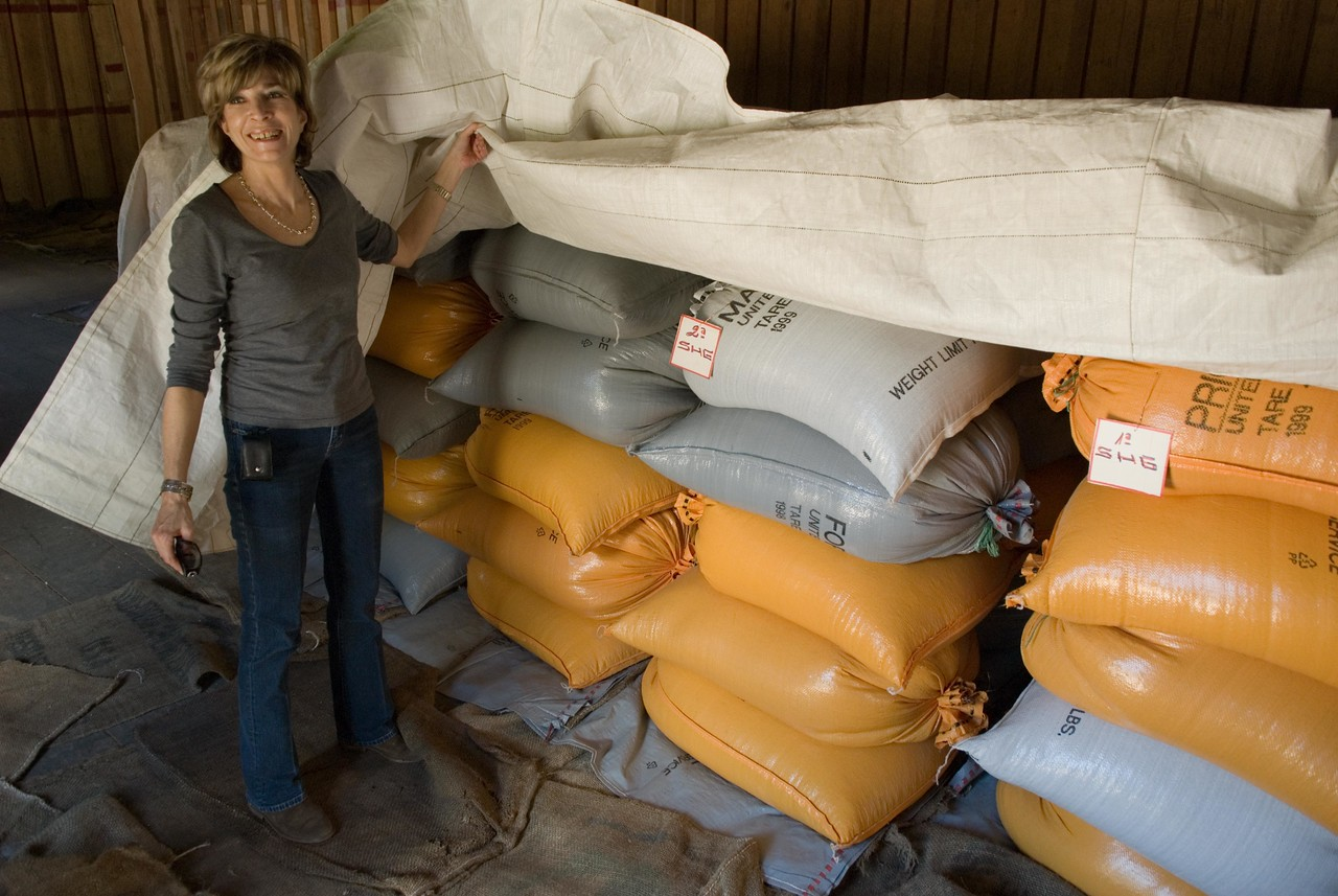 Vickie is standing next to coffees in parchment that are ready to be hulled, sorted and then exported.