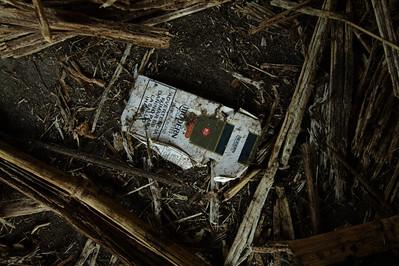 A discarded cigarette box sits among scraps of pressed sugar cane.  El Salvador, 2010