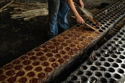 A man molds panela, a sweetener refined from sugar cane juice.  El Salvador, 2010