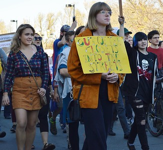 """Young woman carries sign """"Out of The Closets and Into The Streets"""", while marching in protest against President-Elect Donald Trump."""